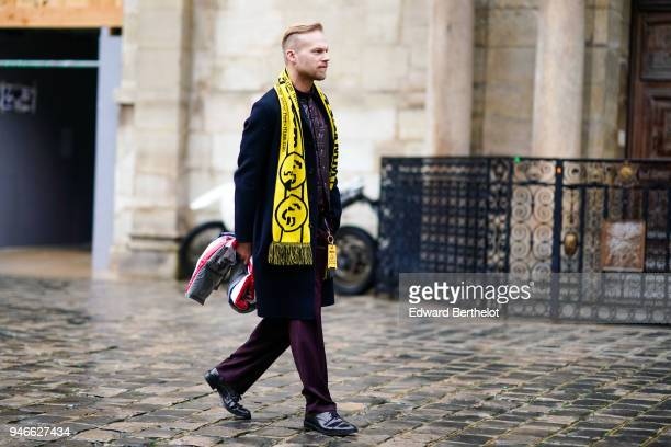 A guest wears a yellow scarf a blue coat purple pants black leather shoes outside Thom Browne during Paris Fashion Week Menswear Fall Winter 20182019...