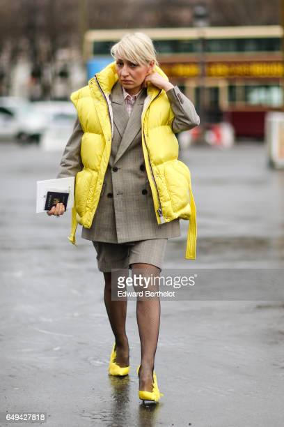A guest wears a yellow sleeveless puffer jacket and yellow shoes outside the Chanel show during Paris Fashion Week Womenswear Fall/Winter 2017/2018...
