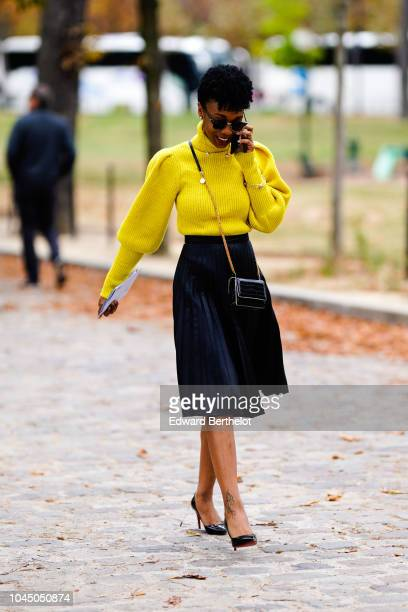A guest wears a yellow wool pullover a skirt a black bag outside Beautiful People during Paris Fashion Week Womenswear Spring/Summer 2019 on October...