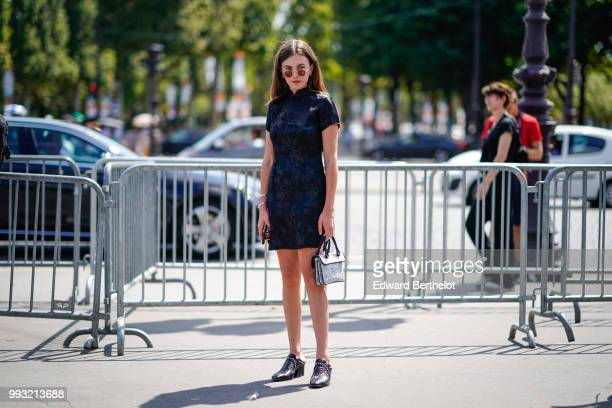 A guest wears ablack dress with embroidered black flowers outside Chanel during Paris Fashion Week Haute Couture Fall Winter 2018/2019 on July 3 2018...