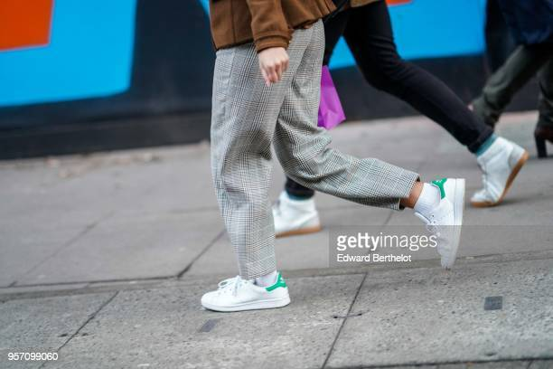 A guest wears Adidas Stan Smith sneakers shoes gray pants during London Fashion Week Men's January 2018 at on January 6 2018 in London England