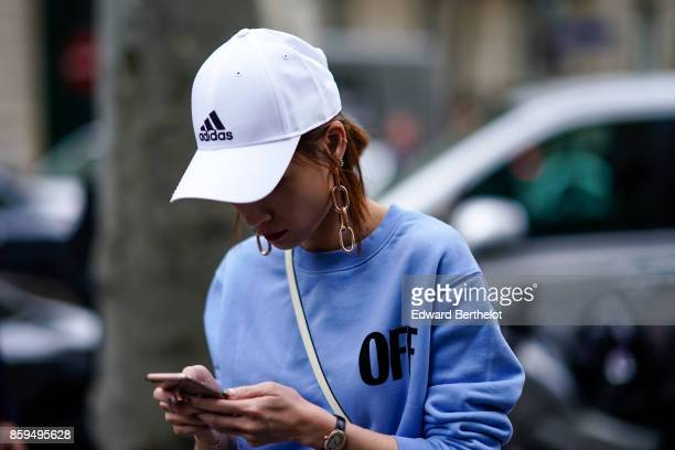 Guest wears an Adidas white cap and a lavender blue sweat shirt, outside Chloe, during Paris Fashion Week Womenswear Spring/Summer 2018, on September...
