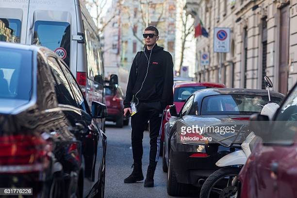 A guest wears an all black outfit including a Zemfira sweatshirt and Adidas track pants during Milan Men's Fashion Week Fall/Winter 2017/18 on...