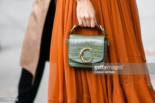Guest wears an almond-green crocodile pattern Chloe handbag, a rust-color gathered and ruffled flowing long skirt, outside Chloe, during Paris...