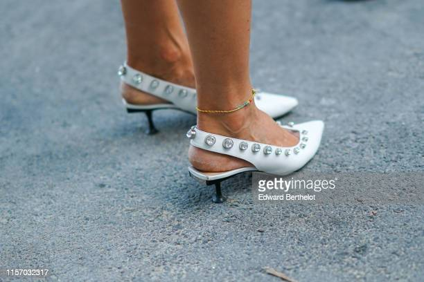 Guest wears an anklet, white pointy bejewelled slingback pumps, outside AMI, during Paris Fashion Week - Menswear Spring/Summer 2020, on June 18,...