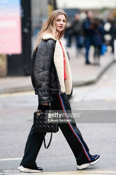 A guest wears an aviator jacket sportswear pants with blue red white printed stripes sneakers and a Lady Dior black bag during London Fashion Week...