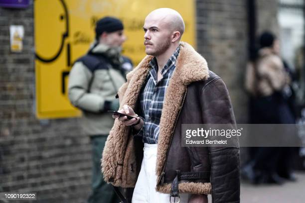 A guest wears an aviator jacket with sheep wool inner lining a blue checked shirt during London Fashion Week Men's January 2019 on January 05 2019 in...