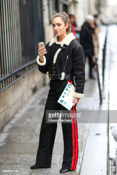 A guest wears an aviator jacket with white fur inner lining and black sportswear pants with red stripes outside the JOUR/NE show during Paris Fashion...