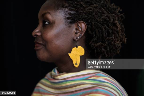 A guest wears an earring in the shape of Africa as she arrives to attend the African premier of the Marvel film 'Black Panther' in Kisumu Kenya on...