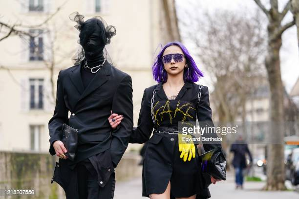 A guest wears an integral black face mask/hood covering the entire head face and neck with attached lace and mesh parts a metallic necklace a black...