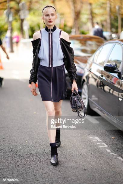 A guest wears an off shoulder jacket with black sleeves a skirt outside Moncler during Paris Fashion Week Womenswear Spring/Summer 2018 on October 3...