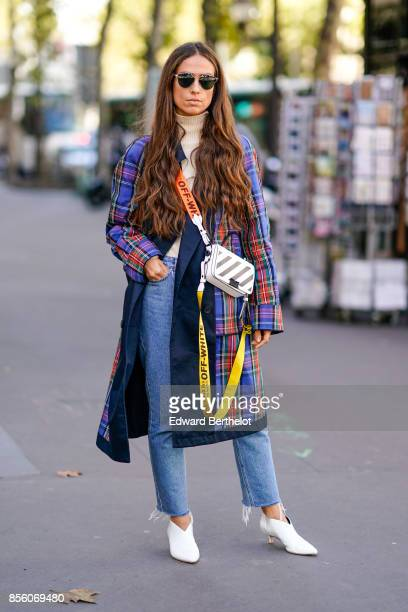A guest wears an Off White bag a tartan coat jeans white shoes outside Acne Studios during Paris Fashion Week Womenswear Spring/Summer 2018 on...