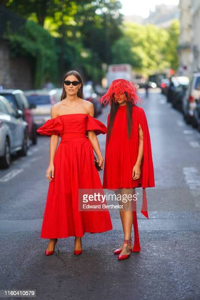 A guest wears an offshoulder red dress with ruffles red shoes Gilda Ambrosio wears a fringed hat a red dress red shoes outside Valentino during Paris...