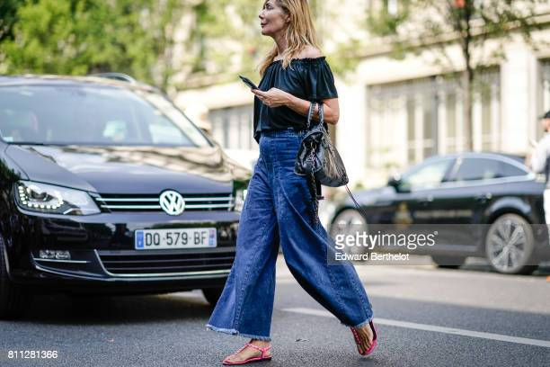 A guest wears an offshoulder ruffle top blue denim large flare jeans pants pink flat sandals outside the Y/Project show during Paris Fashion Week...