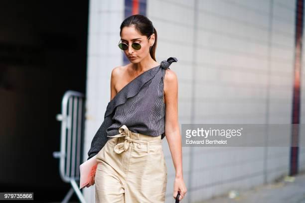 A guest wears an offshoulder striped top beige pants a bag outside Acne during Paris Fashion Week Menswear SpringSummer 2019 on June 20 2018 in Paris...