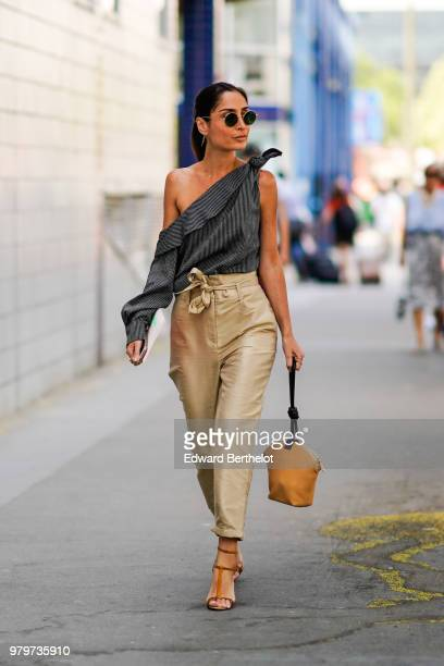 A guest wears an offshoulder striped top beige pants a bag outside Acne during Paris Fashion Week Menswear SpringSummer 2019 on June 20 2018 in Paris...