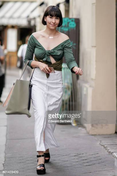 A guest wears an offshoulder top white pants black shoes outside the Thom Browne show during Paris Fashion Week Menswear Spring/Summer 2018 on June...