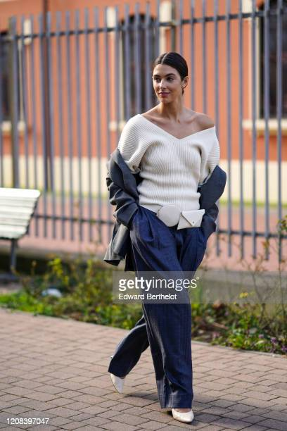 Guest wears an off-shoulder white wool pullover, a belt bag, a gray jacket, blue flared pants, white pointy shoes, outside BOSS, during Milan Fashion...