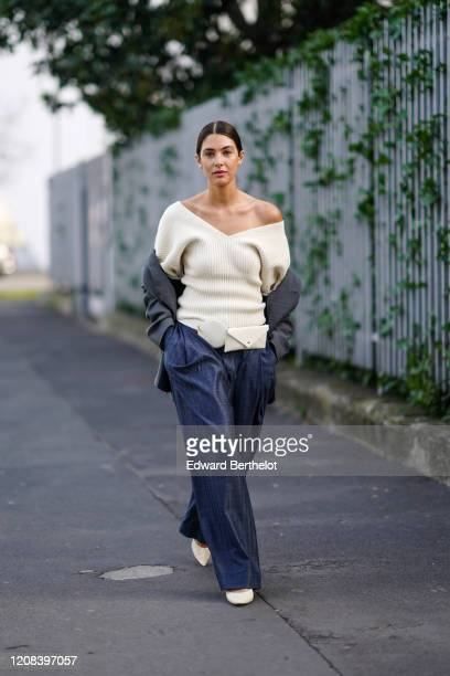 A guest wears an offshoulder white wool pullover a belt bag a gray jacket blue flared pants white pointy shoes outside BOSS during Milan Fashion Week...