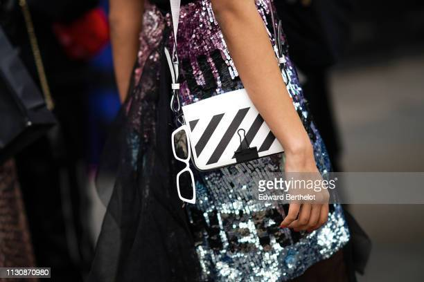 A guest wears an OffWhite striped bag during London Fashion Week February 2019 on February 19 2019 in London England