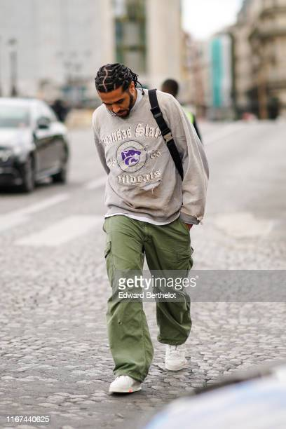 """Guest wears an old ripped sweatshirt with the inscription :""""Kansas State University"""", ripped khaki cargo pants , white sneakersoutside Vuitton,..."""