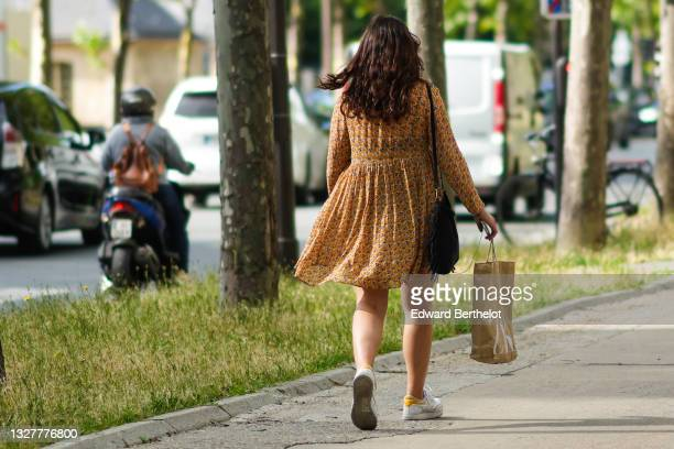 Guest wears an orange and navy blue flower print pattern puffy sleeves ruffled short dress, a black leather fringed shoulder bag, white and yellow...