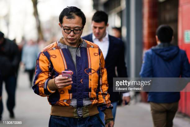 A guest wears an orange and navy blue jacket during London Fashion Week February 2019 on February 19 2019 in London England