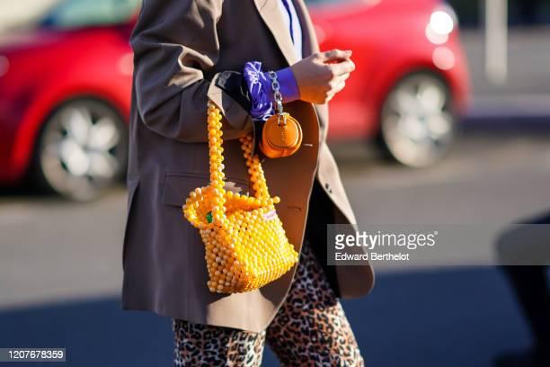 Guest wears an orange beaded bag, outside Prada, during Milan Fashion Week Fall/Winter 2020-2021 on February 20, 2020 in Milan, Italy.