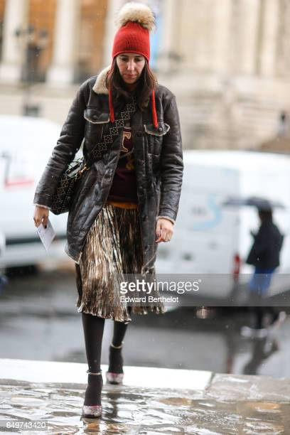 A guest wears an orange beanie hat with a pompom an aviator jacket a pleated skirt outside the Elie Saab show during Paris Fashion Week Womenswear...