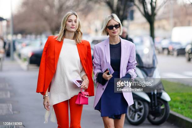 Guest wears an orange blazer jacket, a white wool pullover, a pink bag, golden earrings ; Lisa Hahnbueck wears sunglasses, a pale purple/mauve...