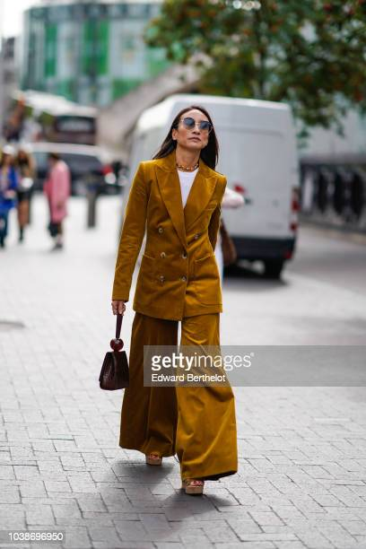 A guest wears an orange blazer jacket orange flare pants during London Fashion Week September 2018 on September 16 2018 in London England