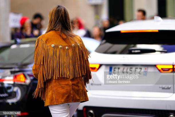 A guest wears an orange brown fringed jacket outside APC during Paris Fashion Week Womenswear Spring/Summer 2019 on October 1 2018 in Paris France