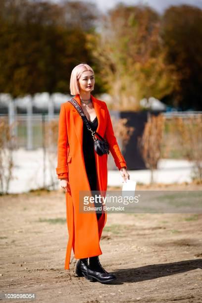 A guest wears an orange coat a Dior bag outside Dior during Paris Fashion Week Womenswear Spring/Summer 2019 on September 24 2018 in Paris France