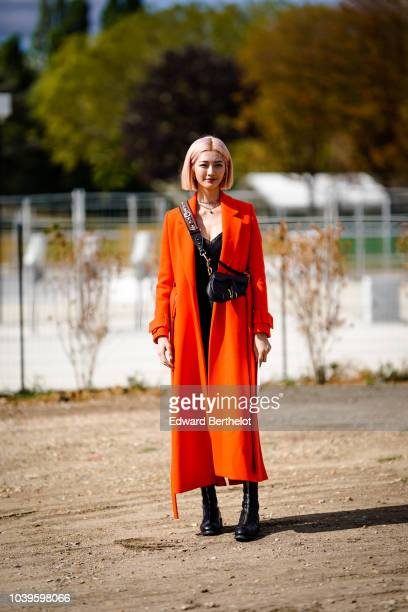 A guest wears an orange coat a Dior bag outside Dior during Paris Fashion Week Womenswear Spring/Summer 2019 on September 24 2018 in Paris France