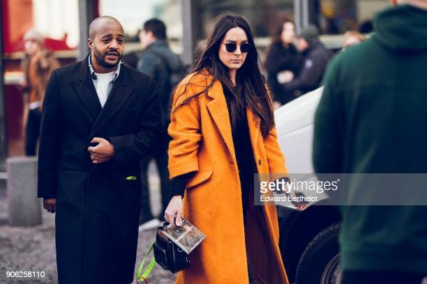 A guest wears an orange coat outside Off White during Paris Fashion Week Menswear Fall Winter 20182019 on January 17 2018 in Paris France
