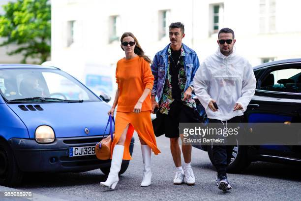A guest wears an orange dress and white boots outside 1017 ALYX 9SM during Paris Fashion Week Menswear SpringSummer 2019 on June 24 2018 in Paris...