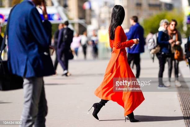 A guest wears an orange dress outside Giambattista Valli during Paris Fashion Week Womenswear Spring/Summer 2019 on October 1 2018 in Paris France