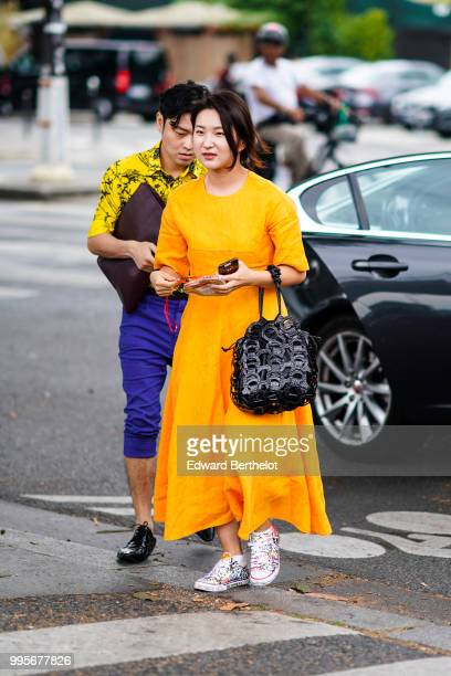 Guest wears an orange dress, sneakers shoes, a black bag , outside Vetements, during Paris Fashion Week Haute Couture Fall Winter 2018/2019, on July...