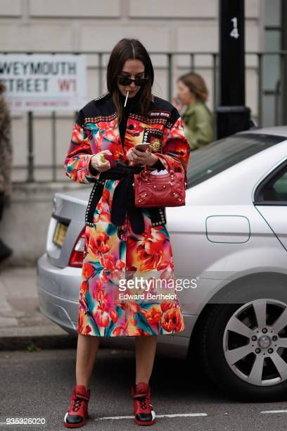 A guest wears an orange floral print Aline dress with black studded inserts a red handbag red sneakers during London Fashion Week February 2018 on...
