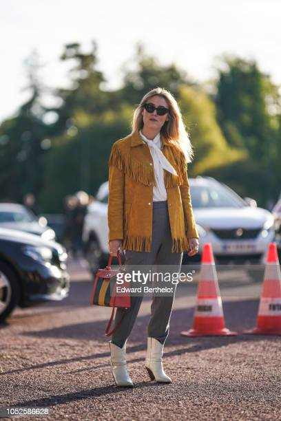 A guest wears an orange fringed jacket white top white leather boots a bag outside Hermes during Paris Fashion Week Womenswear Spring/Summer 2019 on...