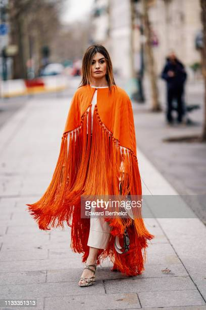 A guest wears an orange fringed poncho outside Altuzarra during Paris Fashion Week Womenswear Fall/Winter 2019/2020 on March 02 2019 in Paris France