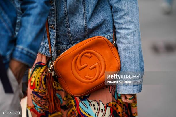 A guest wears an orange Gucci bag and a blue denim jacket outside the Gucci show during Milan Fashion Week Spring/Summer 2020 on September 22 2019 in...