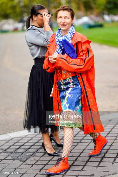 A guest wears an orange hooded raincoat a blue flower print scarf a multicolored skirt fishnet tights and orange shoes outside Manish Arora during...