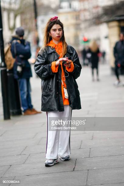 A guest wears an orange hoodie a black leather jacket white flare pants gray sneakers during London Fashion Week Men's January 2018 at on January 6...