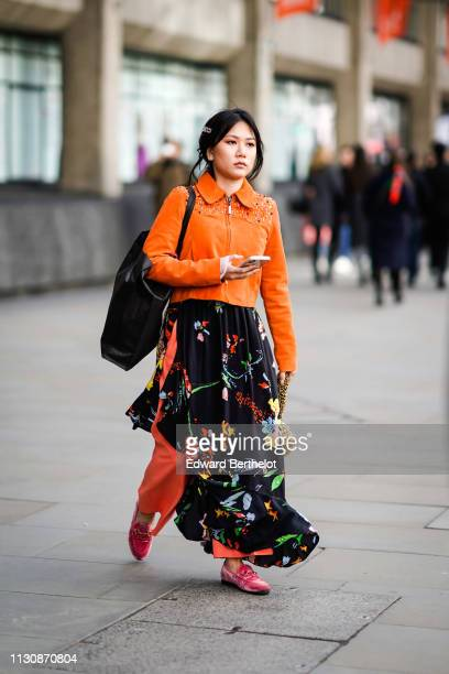 A guest wears an orange jacket a black floral print flowing skirt pink shoes a black bag hair brooch from Gucci during London Fashion Week February...