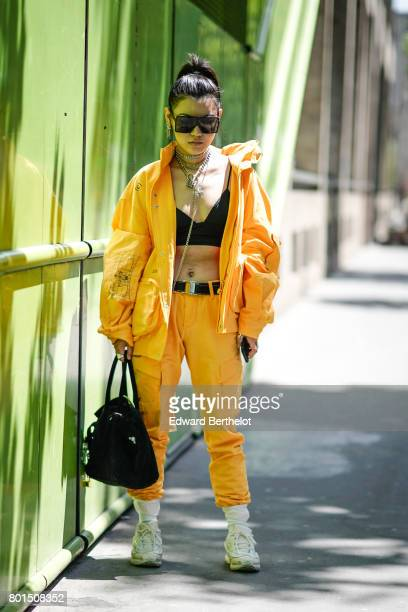A guest wears an orange jacket orange pants white shoes black bras sunglasses outside the Y3 show during Paris Fashion Week Menswear Spring/Summer...