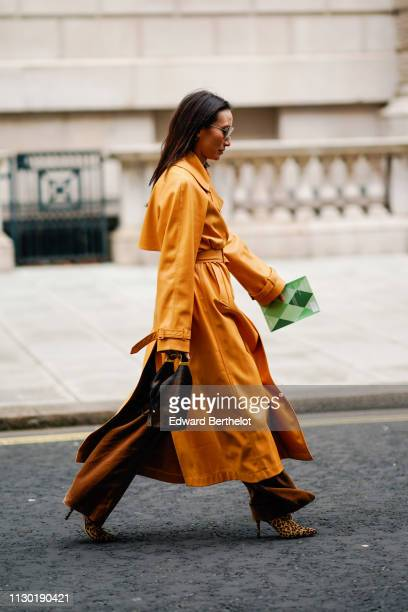 A guest wears an orange leather trench coat during London Fashion Week February 2019 on February 16 2019 in London England