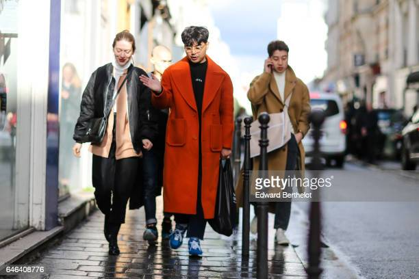 A guest wears an orange long coat outside the AALTO show during Paris Fashion Week Womenswear Fall/Winter 2017/2018 on February 28 2017 in Paris...
