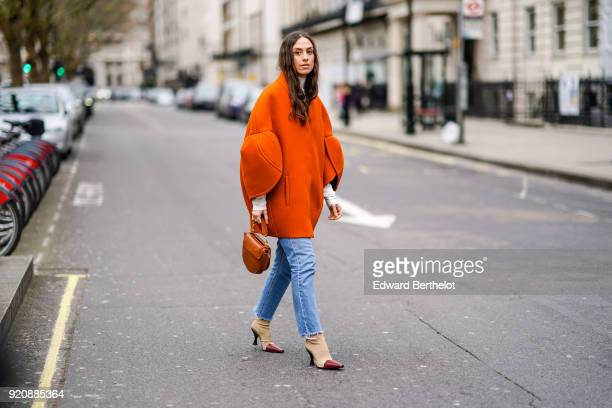 A guest wears an orange oversized coat a brown bag during London Fashion Week February 2018 on February 18 2018 in London England