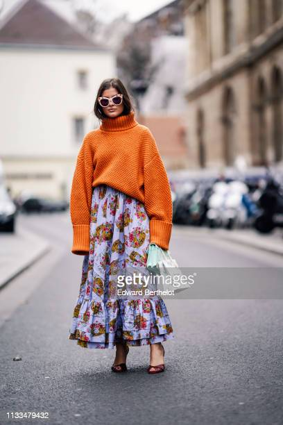 A guest wears an orange oversized pullover a purple floral print pleated skirt sunglasses a bag outside Paul Joe during Paris Fashion Week Womenswear...